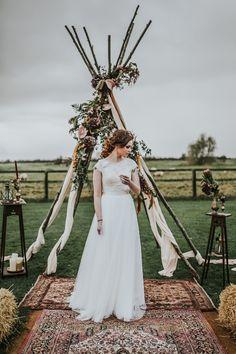 Un tipi avec fleurs et tissu drapé pour une cérémonie romantique