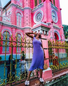 @sgturningpoint Black girl wearing a purple dress posing in front of the pink church in Ho Chi Min City, Vietnam.