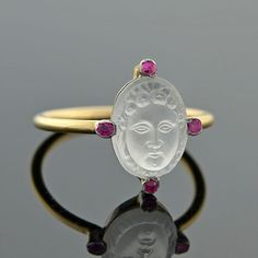 What a beauty!!  A carved moonstone cameo face, delicate ruby accents, and a 14kt yellow gold band. This Art Nouveau ring is gorgeous!