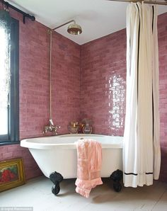 bathroom pink tile suround with stand alone corner footed tub and overhead rain shower head
