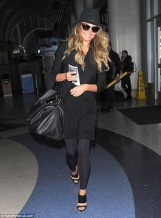 Jet-set chic: Chrissy Teigen worked a flattering head-to-toe black look as she made her wa...