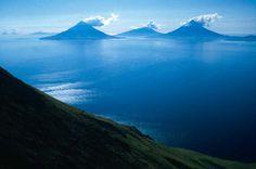 Three, steaming, volcanic islands protrude from the ocean far below. - Wilderness:Aleutian Islands Wilderness Description:Alaska maritime national wildlife refuge
