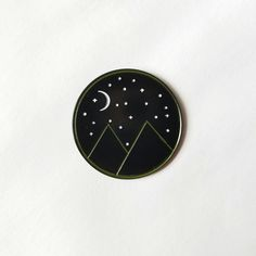 Black and white enamel lapel pin of mountains, a starry sky and a crescent moon