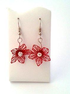 Die Ohrringe sind mit einer geklöppelten Blüte gearbeitet. Der Klöppeldraht ist rot farblich lackiert.Die Perle in der Mitte hat eine silbrige Farb...