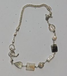 Gemstone necklace with rutile quartz, tourmalinated quartz, aquamarine, ocean jasper, freshwater pearl and India silver beads all wired together with a length of handmade sterling silver chain to form