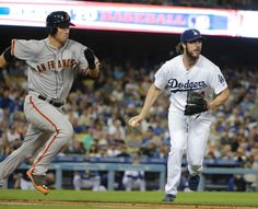 Los Angeles Dodgers starting pitcher Dan Haren, right, looks to throw to first base after fielding a bunt hit by San Francisco Giants' Joe Panik, left, during the third inning of a baseball game Monday, Sept. 22, 2014, in Los Angeles. (AP Photo/Jae C. Hong)