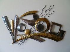 Een groot metalen object als kunststuk aan de muur.