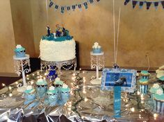 """I showcased the cake and cupcakes with this gorgeous cake stand from Lamps Plus and I found these pretty matching candle holders that I placed a cupcake on top of.. The blue oversized clothes pin is holding a description of this table """"Sven's Sweets"""".. I printed a picture of Sven from the internet and found pretty snowflake themed paper at Michael's and cut to size.."""