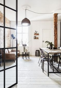 Copenhagen based apartment with a bright living room featuring a cool brick wall and rustic furniture.