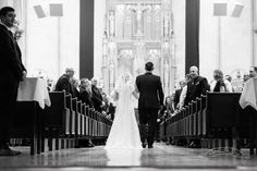 A beautiful black and white shot of the long walk down the aisle with the bride and her father at Gesu in Milwaukee, by Front Room Photography