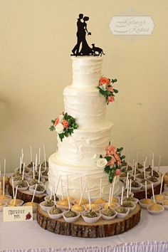 Rustic wedding cake with fresh flowers and cake topper with cat.