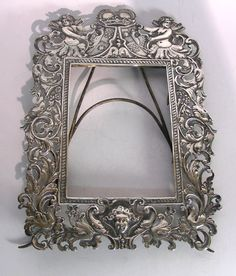 """Rare Antique Silver Frame - Liegnitz, Germany Circa 1750 profusely decorated W/Floral & foliage ornaments, 2 cherubs at top of frame holding a coat of arms under a crown, hinged support easel back - marked W/German silver marks for city of Liegnitz (crossed keys) (then Prussia, today Poland) & maker mark """"MS"""" can hold up to 14x10 cm /5.5""""x4""""-actual D's: 26cm x 18.5cm/10.23"""" x 7.28"""" via 'liveauctioneers.com'♥❤♥"""