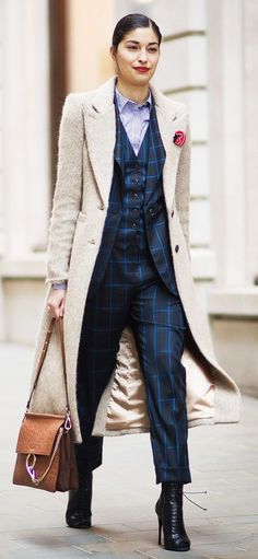 Carolina Issa in a matching plaid suit and cream-colored duster coat