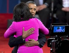 Embrace: The First Couple hugged after the debate, with Mrs Obama, like her counterpart, dressed in pink