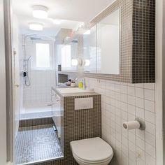 Cette petite salle de bain est aménagée en longueur. Des WC au meuble vasque jusqu'à la douche tout est pensé pour un gain de place optimal.