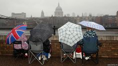 Royal revellers wait in the rain on the South Bank of the River Thames, London, for the start of the Diamond Jubilee river pageant