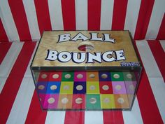 Carnival Games player drops two bouncy  balls in the box.  if landing on same color then you win.
