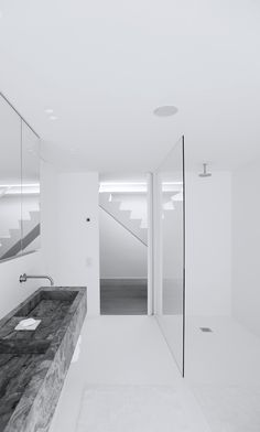 Minimalist Bathroom // all white with a modern glass shower and dark stone counter in this Bathroom by Govaert & Vanhoutte