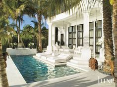 White alabaster stone covers this patio, extending into the pool making lounging extra stylish.