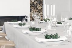Use your wreaths to adorn a table set with white linens, white plates, white candles, silver flatware and candelabras, and classic wineglasses, as seen on Stylizimo.