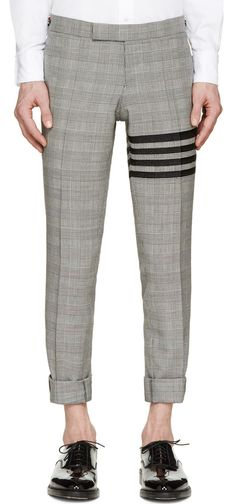 Grey Glenplaid Signature Stripe Trousers by Thom Browne. Slim-fit pleated trousers in black and white with glenplaid pattern throughout. Buttoned cinch tabs at waistband in signature blue, white, and red stripes. Raw ankle cuffs, made from wool, perfect for semi formal occasion. http://www.zocko.com/z/JJMTJ