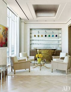 One corner of the living room features a bronze bar with a white onyx top and, behind it, shelves filled with Lalique vases and Baccarat glassware | archdigest.com