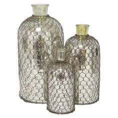 Set of three glass bottles with metal mesh covers.    Product: Small, medium and large bottleConstruction Material: ...
