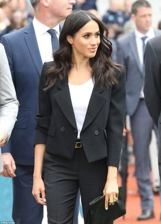 Meghan wore a black tailored trouser suit complete with a cropped jacket and a simple whit...