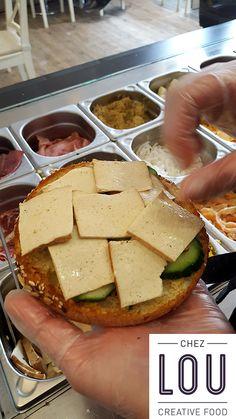 Regardez, vous assistez à la naissance d'un bagel végan... La main experte de Lou a tranché un bagel (ici multi-céréales) en 2, et a déjà disposé sur le fond du concombre bio. Le tofu fumé bio vient le recouvrir généreusement.  Ce sera au tour du poivron grillé bio, de la coriandre et des graines de sésame (tout bio), puis d'un filet de sauce curry-mangue. On referme le bagel, et le végan est né. Il ne reste plus qu'à le dévorer ! =D Un bagel pour les végan et tous les gourmands