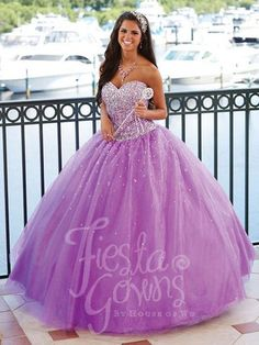 A two-piece ball gown crowned by a heavily beaded bodice composed of symmetrical beadwork, beaded illusion neckline, and straps, with the back clasping via hook and eye. The ball gown skirt features i