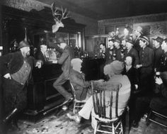 "Patrons gather around the bar inside of a saloon in the mining town of Turret, Chaffee County, Colorado. ""Whiskered man (left end of bar) old man H. M. Zook. C. W. Franzce is man holding beer glass which appears directly over cap of card player whose hand is exposed."" Date [between 1900 and 1910?]"