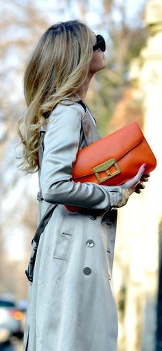 street style / gray trench + orange color pop clutch purse