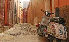 """Along the western coast of Sardinia, Bosa was once a busy town with a healthy local economy centered on leather production. It is now a sleepy fishing village with brightly-colorored crumbling buildings and cracked cobblestone streets. Here, a much loved and worn scooter rests along a narrow corridor between homes, painted over in colors that echo the town."" (From: 35 Beautiful Images of Italy)"