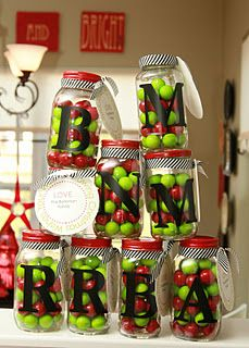 Clean jars, spray paint lids any color, stick on first letter of recipient's last name, fill with goodies, add ribbon and tag.