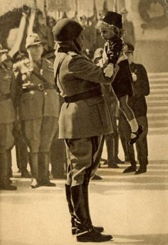 World War II. Italian fascist propaganda, postcard showing Mussolini with a child in the arms of youths in uniform fascists (Italy). Ca. 1941.