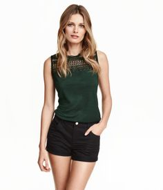 (in black) Sleeveless top in soft jersey with lace at front, opening at back of neck with a button, and a rounded hem.