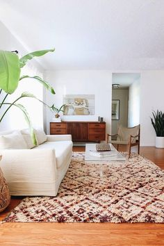 bright white living room with white couch and patterned rug