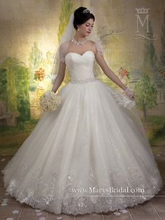 This dress is a dream! Featuring glitttered tulle, silver sequins and thread creating a lace design, flowers with a beautiful crystal center, and a sweetheart neckline. In Stock for try ons!
