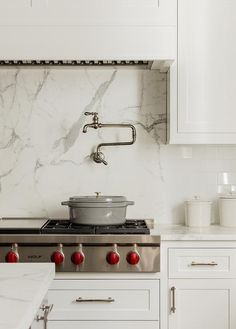 Kohler Artifacts Double-Jointed Swinging Pot Filler accents a cooktop on a statuary marble slab cooktop backsplash under a white wood vent hood in a transitional white kitchen. Ivory Kitchen Cabinets, Kitchen Cabinet Layout, Glass Front Cabinets, Marble Herringbone Tile, Kohler Artifacts, Kitchen Vent Hood, Rivera, Erin Gates, Pot Filler