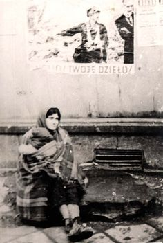Warsaw ghetto Poland, A woman in tatters sitting on the sidewalk in the ghetto.