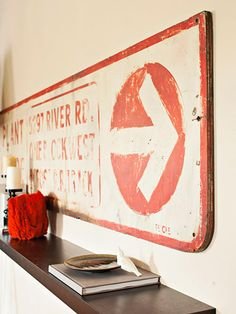 Small-Space Bungalow on a Budget Finders, Keepers: This old plywood sign, salvaged from a nearby manufacturing plant, was a bargain find. It not only pulls in the coral hue from the adjacent sunroom, it's also a great dinner conversation piece.
