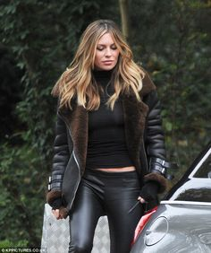 Model figure:She paired her leather trousers with a tight black poloneck that revealed a tantalizing glimpse of her taut tummy