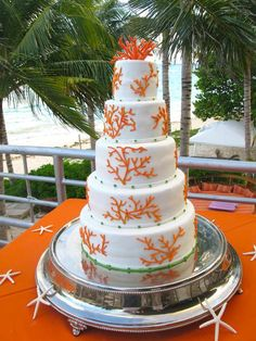 White cake with an orange coral design - perfect for a beach wedding!