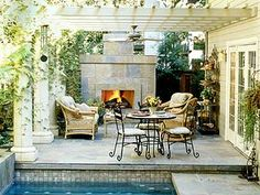 Slate tiled terrace with fireplace.  Love the pergola above and doorway.  Dining table and seating for entertainment and relaxation.