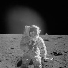 Astronaut Charles Conrad Jr., Apollo 12 commander, using a 70mm handheld Haselblad camera modified for lunar surface usage