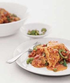 Spanish Chicken and Rice | This take on the classic Spanish arroz con pollo, which cooks in a single saucepan over the stovetop, doesn't disappoint. Succulent chicken, crisp-tender green peppers and peas, and more, all covered in a garlicky-tomato sauce, combine for a filling meal that covers all the food groups. Add pimento-stuffed olives at the last minute, if desired, as you plate each dish. (Plenty of recipes actually require that you add these as you cook; we've left them until the end…
