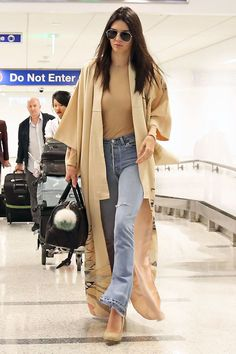 Jenner goes casual chic for her flight from London to Los Angeles wearing a tan bodysuit and distressed flares topped with a camel duster jacket.
