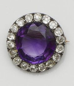 A Victorian amethyst and diamond brooch  Pinched claw set with a circular mixed-cut amethyst to a border of old brilliant-cut diamonds, gold and silver mounted, total diamond weight approximately 1.80ct, diameter 2.4cm.