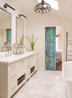 A distressed turquoise barn door opens to an en suite bathroom boasting a sloped ceiling fitted ...