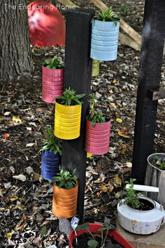 Coffee Cans painted and hung on a post.these would be great in my flower beds with ferns, impatients or hostas